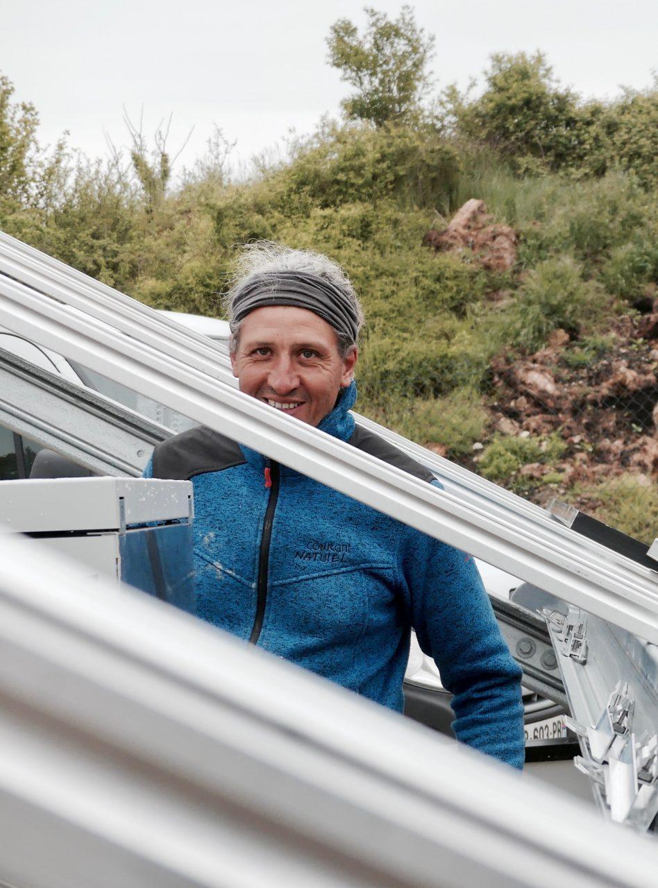 Montage panneaux photovoltaiques, technicienqui sourit.